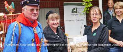 Kiepenkerl Alois Epping und Christine Epping überreichen einen Ableger der Homeraner Ulme an die Stiftung.